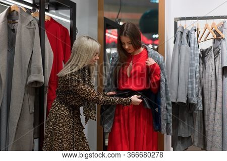 Two Women In Fashion Boutique Choose Red Dress Season A Professional Stylist Helps Customers Choose