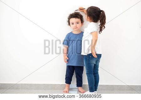 Cute Girl Measuring Height Of A Funny Child With Curly Hair. Sister Measures The Growth Of Her Broth