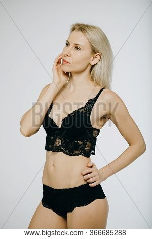 Model Girl Posing In Studio. Joyful Fashion Woman With Black Panties, Black Bra And Sexy Lingerie.
