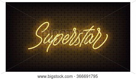 Yellow Neon Superstar, Lettering. Neon Text Of Superstar On Black Brick Background, Night Ambience.