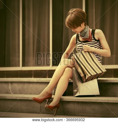 Young woman with shopping bag sitting on the mall steps Stylish fashion model with pixie hair in striped tank top