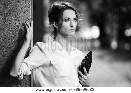 Happy young business woman with clutch bag on city street Stylish fashion model with bun updo hair style in white shirt