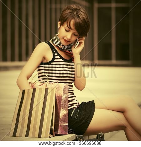 Happy young woman with shopping bag calling on cell phone next to mall windows Stylish fashion model with pixie hair in striped tank top and denim skirt