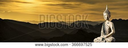 A Small Replica Statue Of The Buddha Against A Dramatic Sunset And Hazy Mountains
