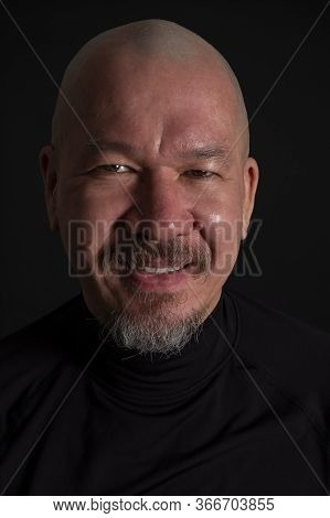 Studio Portrait Of A Handsome Mixed Race Man With A Beard Smiling, On Black Background