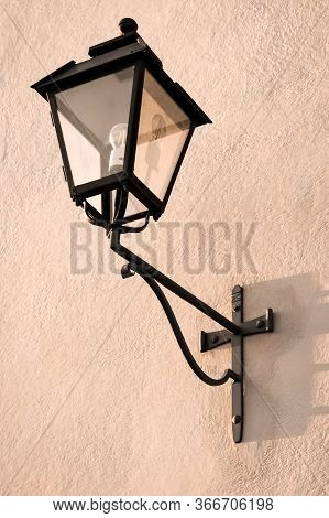 Black Vintage Streetlight On A Pink Wall In A European Town.