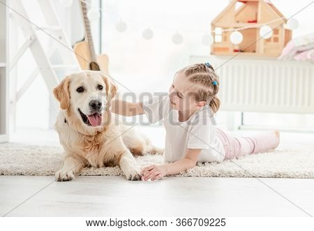 Smiling little girl petting adorable dog in bright room