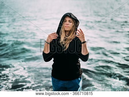 A Girl In A Black Sweater And Blue Jeans Is Standing By The Sea With Eyes Closed And Her Arms Are Ne