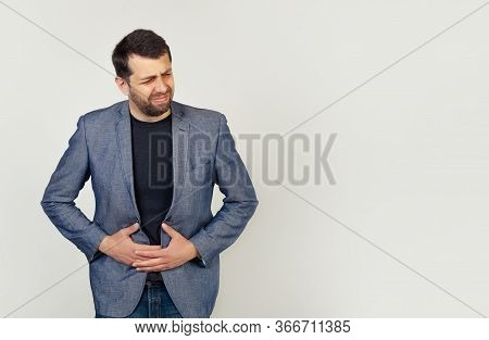 A Young Man With Stomach Trouble, A Man Holds His Hands On His Stomach, Because Upset Stomach And Di