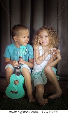 Portrait of a cute kids sitting ouddoor with ukulele