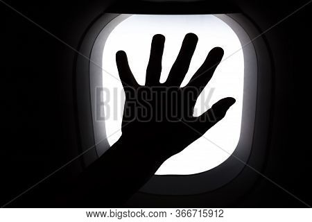 Travel By Airplane. Hand On Window Airplane. Silhouette Of Hand On Window During Flight. Missing Tra