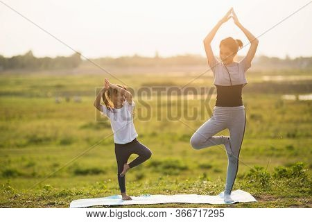 Two Cute Girls Practicing Yoga At Park In Sunny Bright Light.