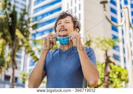 Quarantine Is Over Concept. Man Taking Off Mask Against The Background Of Small Town Houses. We Are