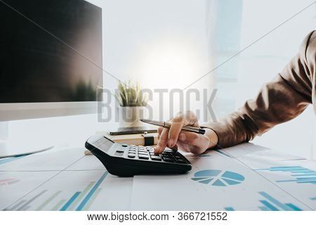 Close Up Of Business Woman Or Accountant Using Calculator During Analysis On Data Paper
