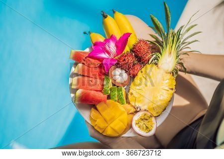 Young Woman Relaxing And Eating Fruit Plate By The Hotel Pool. Exotic Summer Diet. Photo Of Legs Wit