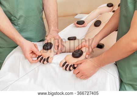 Hot Stones Massage On Female Feet, Toes And Legs In Four Hands At Salon.