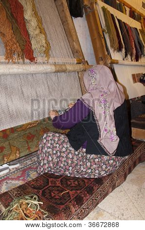 Traditional Islamic Woman Working On A Rug