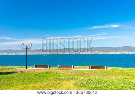 Three Benches On The Sunny Beach Shore. Beautiful Skyline View From Empty Park With Paved Footpath O