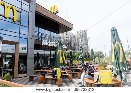 Kiev, Ukraine, May 15, 2020, Glovo Deliveryman Waits To Take Away Order From Mcdonald Restaurant, Qu