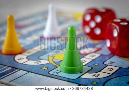 Multi-colored Game Chips With Dice On The Playing Board. Concept Of Leisure Games