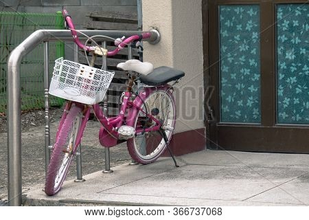 Parked Children's Bike Near The Entrance To The House. Pink Bike Parked In Front Of The Door