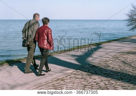 Taganrog, Russia - 07.04.19: Adult Man Walking With His Wife Along The Promenade. Man And Woman Walk
