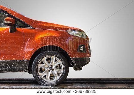 Orange Car With White Soap On The Body In Car Care Shop. Focus On Wing Mirror. Isolated On Grey Back