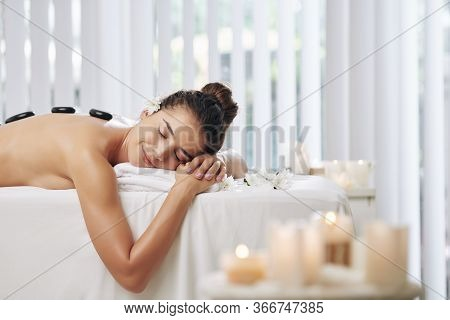 Smiling Beautiful Young Woman Lying On Bed In Spa Salon With Scented Candles Around And Enjoying Hot