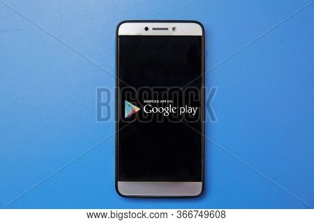 Android Google Play Store Logo On Smartphone Screen On Blue Background. Man Holding Smartphone With