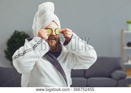 Funny Strange Fat Bearded Man With A Cosmetic Mask On His Face In A Bathrobe Does Spa Treatments On