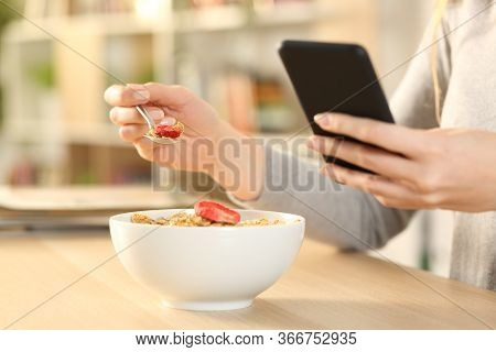 Close Up Of Woman Hands Eating Cereal Bowl With Fruit Checking Smart Phone Sitting On A Table At Hom