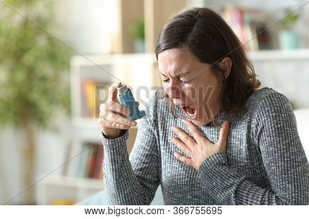 Asthmatic Adult Woman Suffers Asthma Attack Holding Inhaler Sitting On The Couch At Home