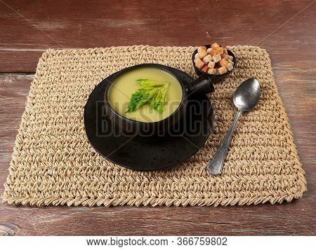 Celery Cream Soup Served In Rustic Brown Bowl With Rustic Cutlery