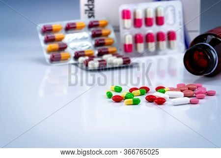 Tablets And Capsules Pills On White Table And Blurred Drug Bottle, Blister Pack, And Antibiotic Drug