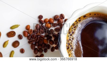 Flat Lay. Banner. Black Coffee With Coffee Foam In A White Cup. In The Background Are Coffee Beans A