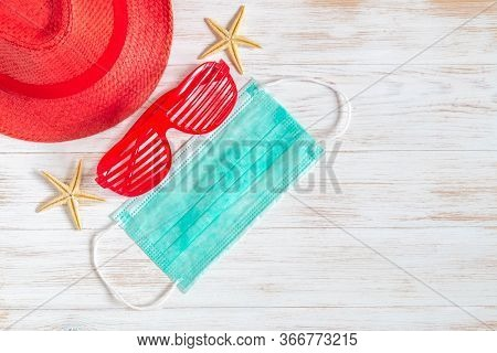 Travel And Vacation Background With Red Hat, Sunglasses, Seashells, Starfish, And Medical Mask On Vi