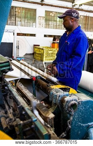 African Factory Worker Operating A Cotton Thread Weft Loom Machine