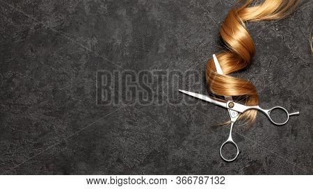 The Hairdresser. Scissors And Curl Of Hair On A Black Background