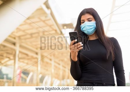 Young Indian Woman With Mask For Protection From Corona Virus Outbreak Using Phone At The Skywalk Br