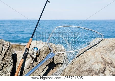 Spinning and fishing net on the rocks by the sea