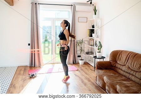 Doing Sports At Home During Quarantine. A Young Woman Jumps With A Skipping Rope Indoors. Cardio Wor