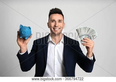 Happy Man With Cash Money And Piggybank On Light Grey Background