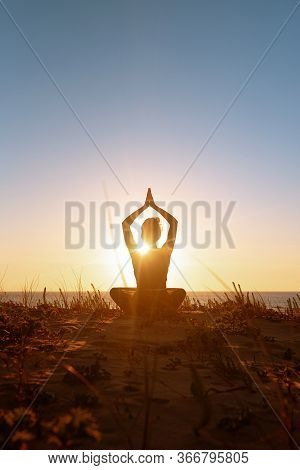 Silhouette Meditation Girl On The Background Of The Stunning Sea And Sunset. Yoga, Fitness And Healt