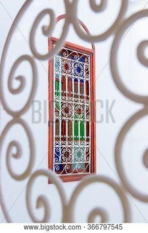 Window With Multi-colored Glass And Arabic Lattice In Marrakesh, Morocco. Moroccan Authentic Interio