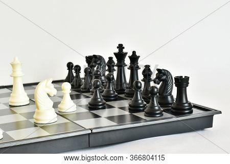 Chess. Chess King Checkmate, The Game Of Chess Is Over. Colorful Chess Pieces On A White Background.