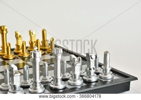 Golden And Silver Chess Pieces On A Chessboard Close-up On A White Background. Checkmate. Queen, Kin