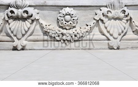 Hprizontal background with ancient carved ornament with flower garland on a stone wall. Mock up template. Copy space for text