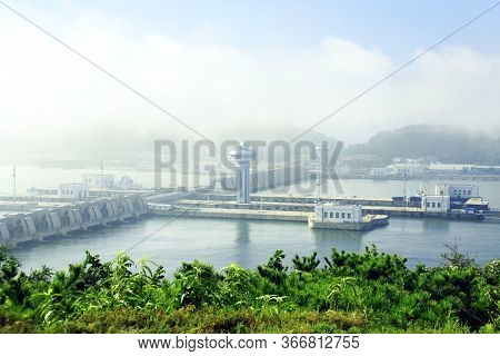 The Nampho Dam (West Sea Barrage) on the river Tedongan, Nampho, North Korea (DPRK). Korean hydroelectric power station West Sea Dam in the morning mist