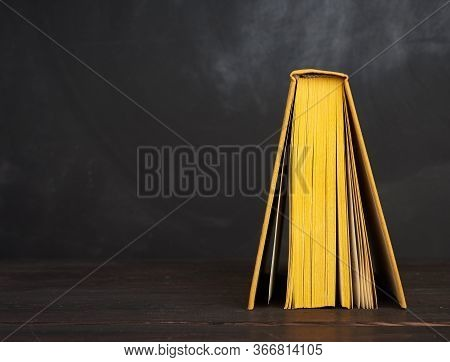 Open Book In Yellow Hardcover Against A Black Chalk Board, Copy Space