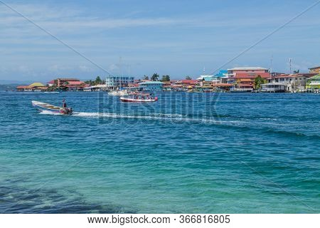 Bocas Del Toro, Panama: August 23, 2019: Tourists at the colorful Caribbean buildings over the water with boats, Bocas del Toro, Panama